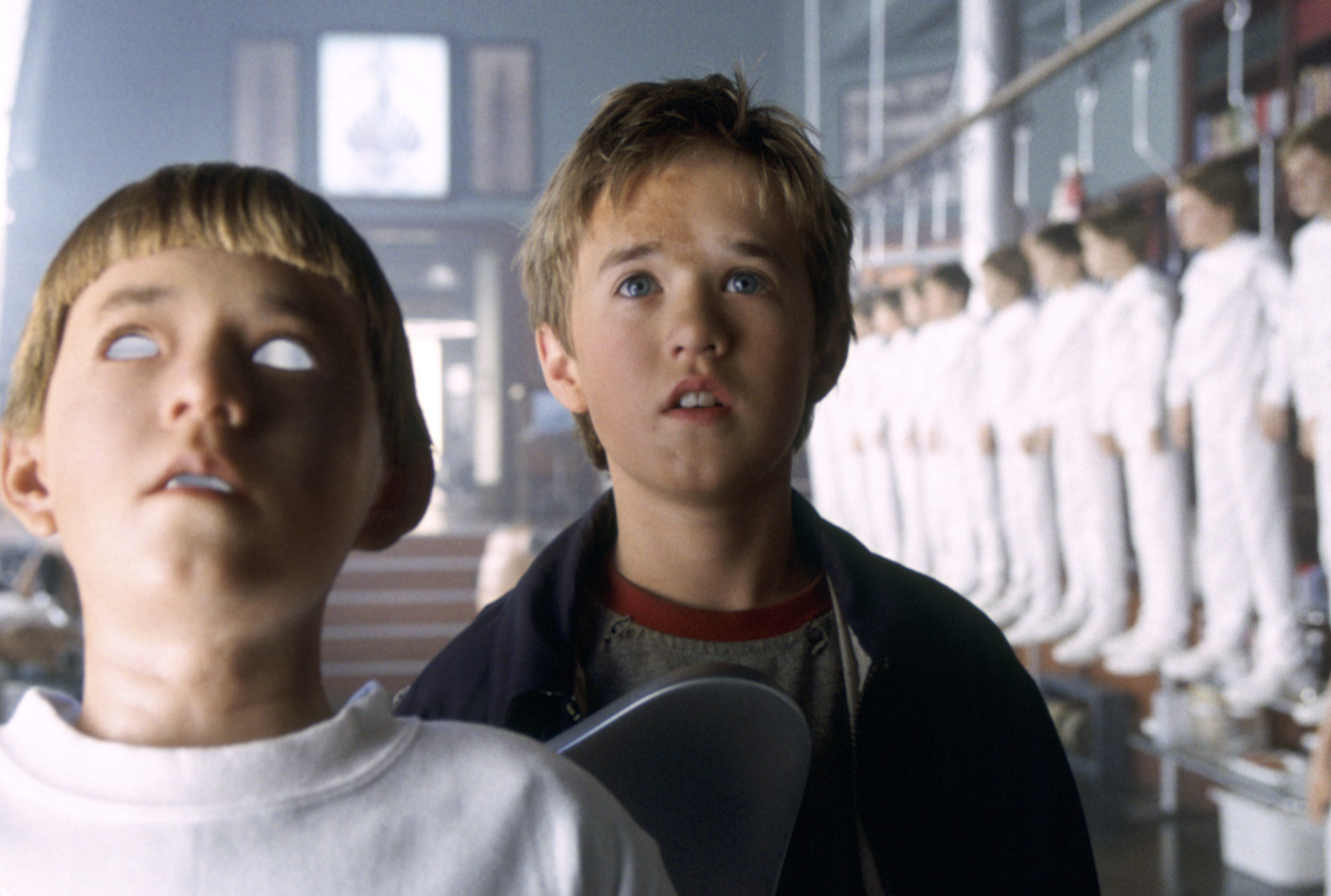 A young child, David, is surrounded by child-like, robotic figures all dressed in white. The one next to him looks very similar to himself.